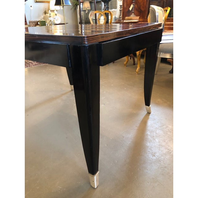 Circa 1930 Maison Sourbrier French Art Deco Macassar ebony dining table with nickel plated bronze feet. Fashioned in the...