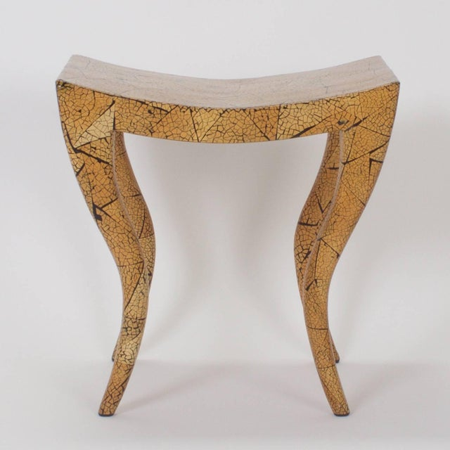 Swank Mid-Century bench or stool with a dramatic Egyptian influenced form and a hip crackled finish in variegated organic...