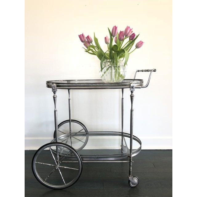 Italian Mid-Century steel polished bar cart with pierced oval gallery containing glass shelf over lower shelf with cast...