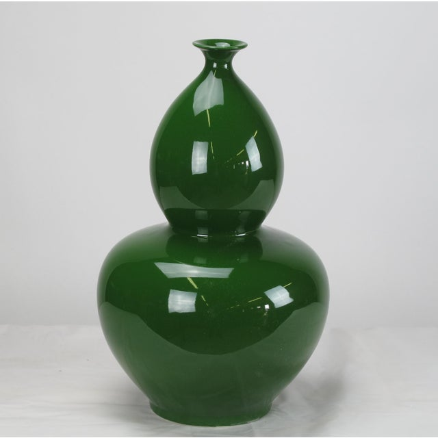 A symbol of immortality and happy life, this bottle gourd vase with glossy deep green finish has smooth curving streamline...