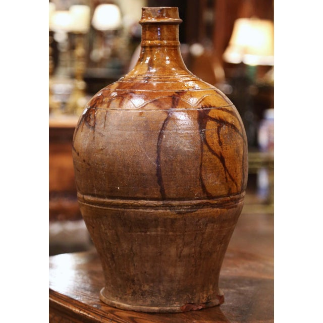 This antique pottery wine bottle was created in Spain circa 1880; made of terracotta with a dark beige glaze and hand...