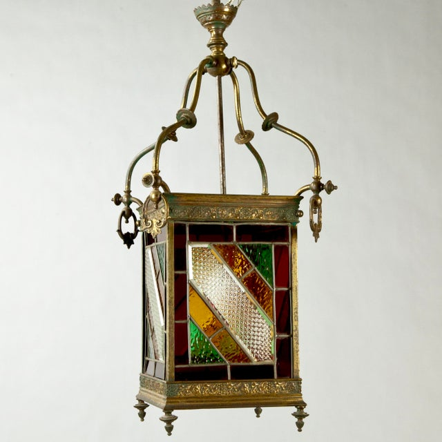 Beautiful late 19th century English brass square framed hall lantern featuring geometric stained glass leaded panels on...