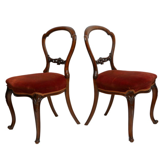 Walnut balloon back side chairs with sinewy carved balloon back and floral and leaf cross brace on cabriole legs ending...