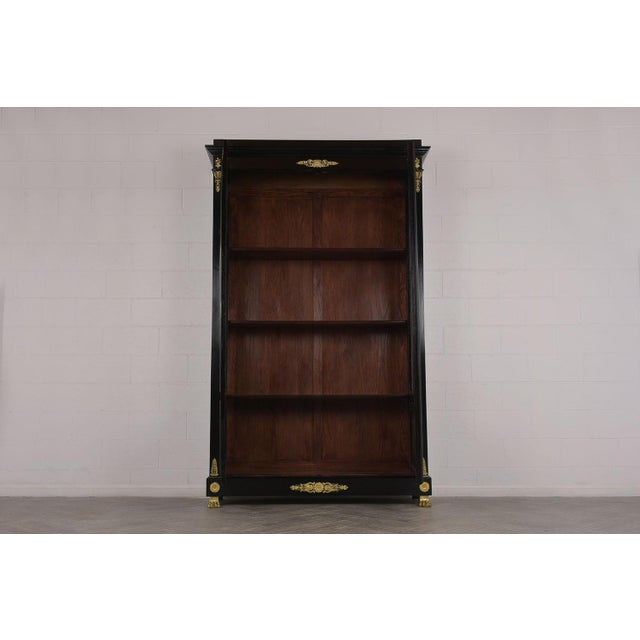 This is a 19th Century French Empire-Style Bookcase. Made from solid mahogany wood, newly ebonized. Has elegant brass...