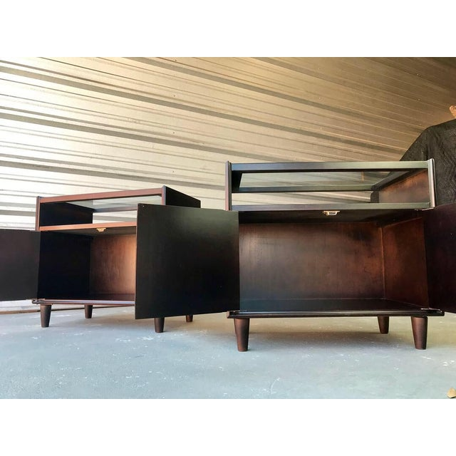 Beautifully restored Mid-Century Modern dark walnut glass top end tables. These two end tables offer two doors that swing...