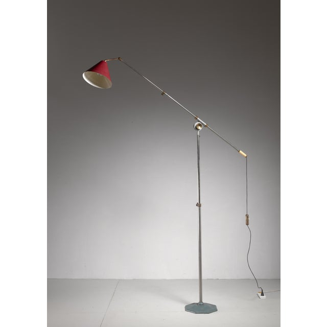 A very large industrial metal floor lamp with a red hood. The lamp is adjustable at many points: the length of both the...