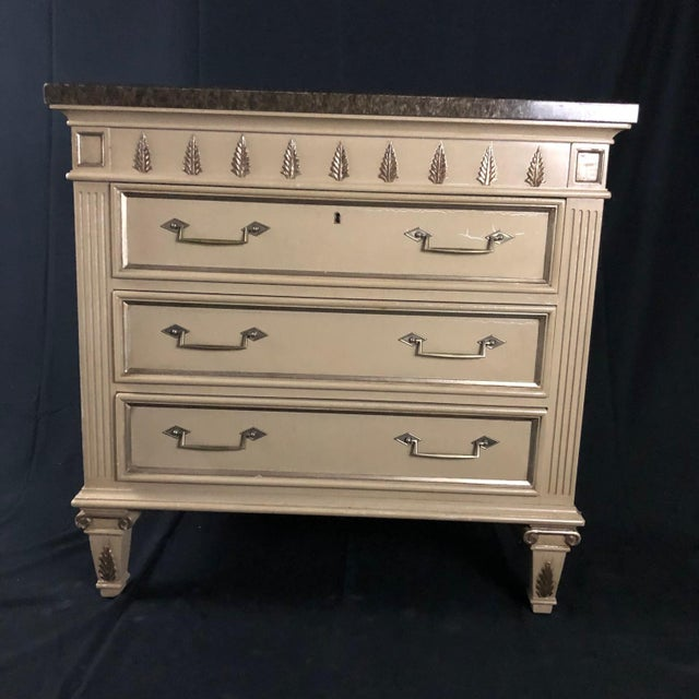 A large and handsome pair of painted mid century chests or night stands constructed of heavy solid wood, painted in an off...