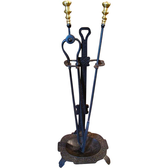 An Arts and Crafts period (1880-1910) cast iron stand, probably American, along with American wrought iron fire tools: a...