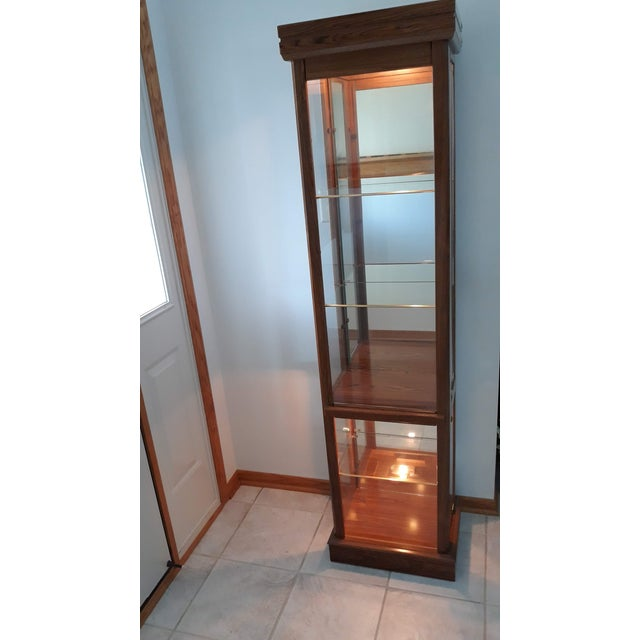 Tall, rectangular, lighted 5-shelf wood curio cabinet The top section has 3 shelves (2 glass/1 wood) and the bottom...