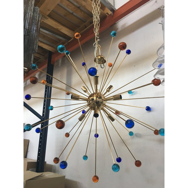 Multicolor Murano glass triedo sputnik chandelier with a gold metal frame. The chandelier is like a sun in multicolors...