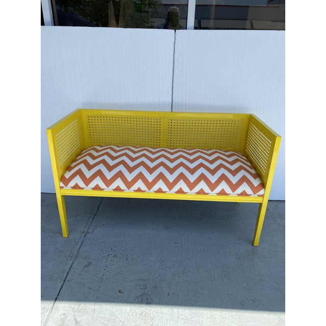 This is newly restored midcentury loveseat in primary yellow color and reupholster in a white and orange chevron fabric .
