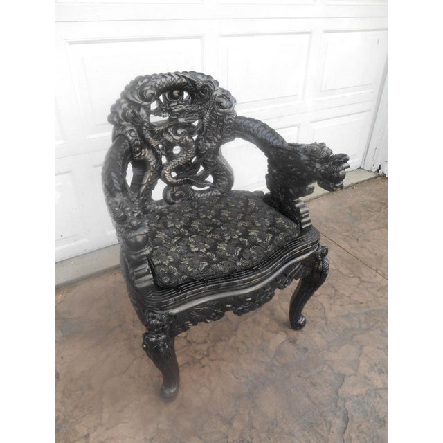 Antique Chinese with relief-carved and pierced back rest of coiled dragon design supported by arm rests of dragon-in-...