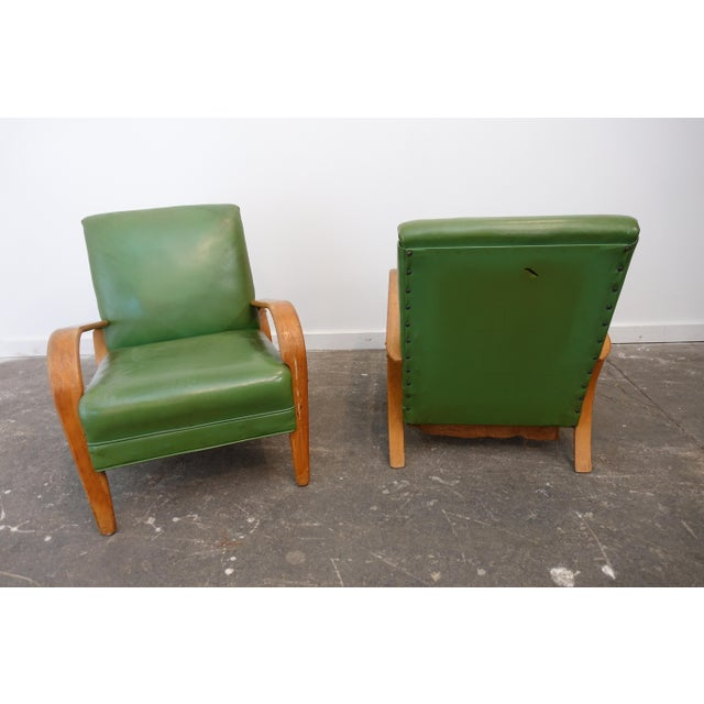 This pair of club chairs has a bent wood frame and are upholstered in a green vinyl. These chairs are structurally sound...
