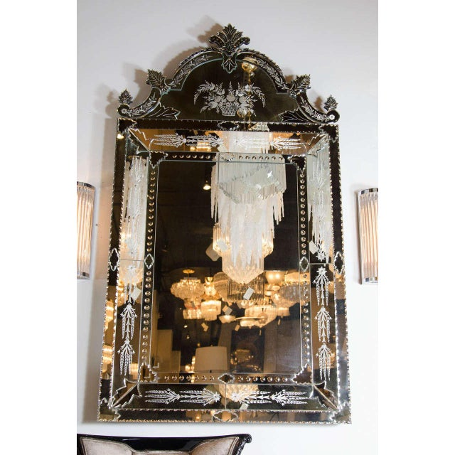 This rare Venetian style mirror features hand beveled and reversed etched floral and stylized foliage detailing. A...
