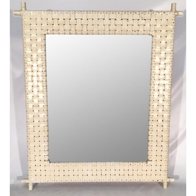 Large bamboo wall mirror features woven leather frame. Good vintage condition with minor abrasions consistent with age.