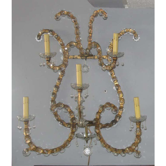 This Pair of glamorous/large scale gilded iron wall sconces each have 5 arms and are overlayed with crystal glass details....