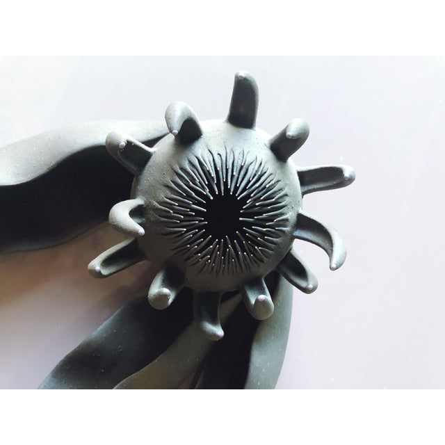 Beautiful, mythological flower sculpture in a thin, unglazed black ceramic. Light color details in orange and purple on...