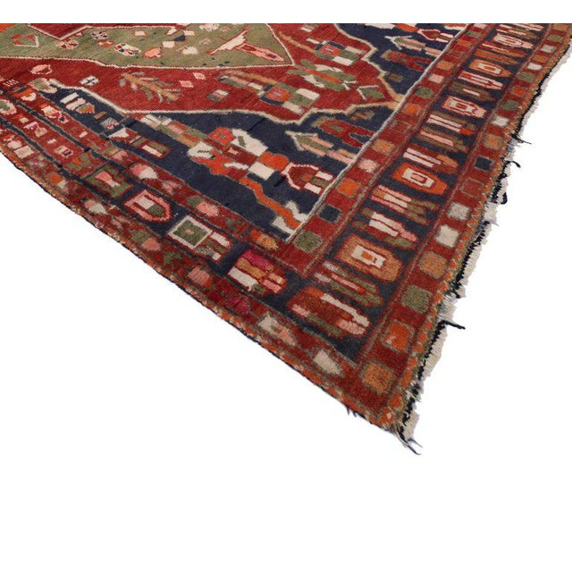 Give your home fashion-forward energy with the dynamic and dramatic look found in this vintage Persian Bakhtiari rug. This...