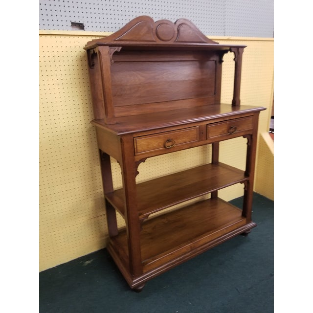 Antique oak dessert server, one shelf on top that is supported by a column on each side, below two drawers with brass...