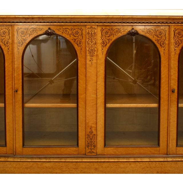 French Charles X maple and rosewood inlaid sideboard cabinet with four arched top doors and white marble top.