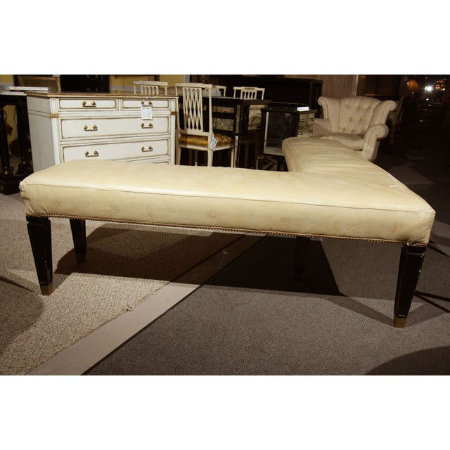 "An intriguing ""L"" shaped bench, upholstered in beige leather with imprinted greek key and medallion stamps. The entire..."