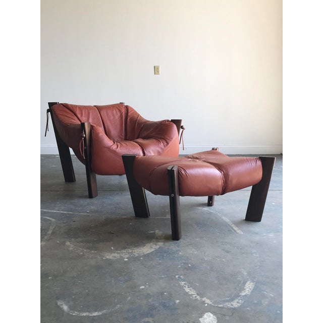 Stunning Percival Lafer chair and ottoman. Model MP-211 in orange leather with a wood frame. Very good condition with...