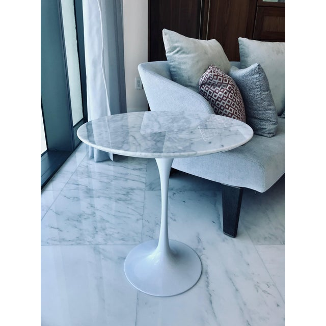 The iconic tulip side table comprised of solid arabescato carrara marble top over a a stylized cast metal base in a white...