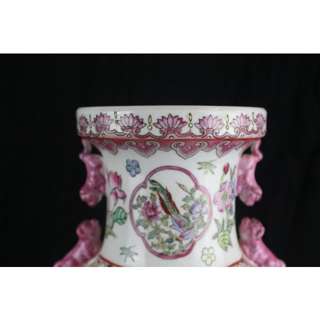 Pink and white Chinese vase with scenes of women, birds, and floral imagery. Pink fu dogs on side.