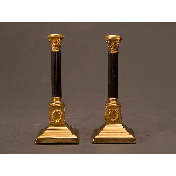 A pair of Empire style bronze doré and patinated bronze candlesticks from the Louis Philippe period in France c. 1850....
