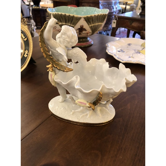 Someone's favorite pretty white and gilded porcelain dish having lovely scalloped edge bowl with cherub holding a gold...