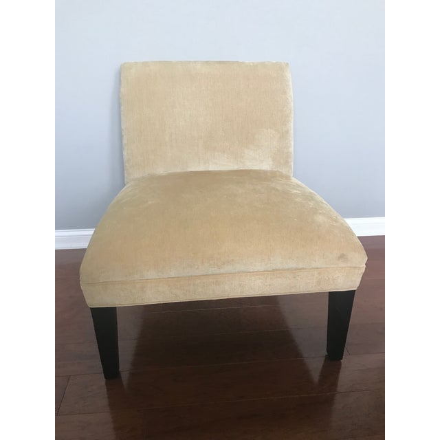 Slipper chair by Mitchell Gold + Bob Williams. Upholstered in a pale, buttery yellow material that stand on tapered...