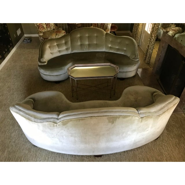 Rare pair of beautifully curving silhouettes that will make a statement in any home. The 1940s pair of sofas (one from...
