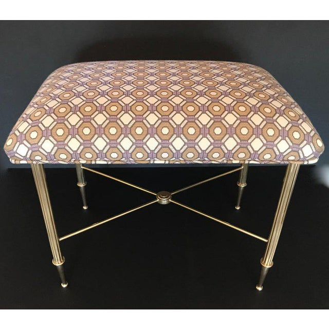 French brass bench or stool with reeded brass legs, stylized tapered feet and X cross bar with newly upholstered top....
