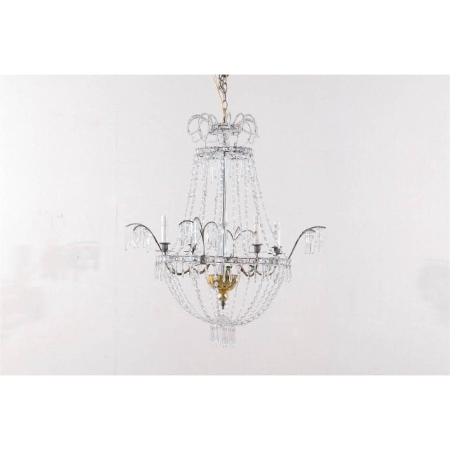 This early 20th century Italian four-light chandelier is made of a crystal central column with accents of gold mercury...