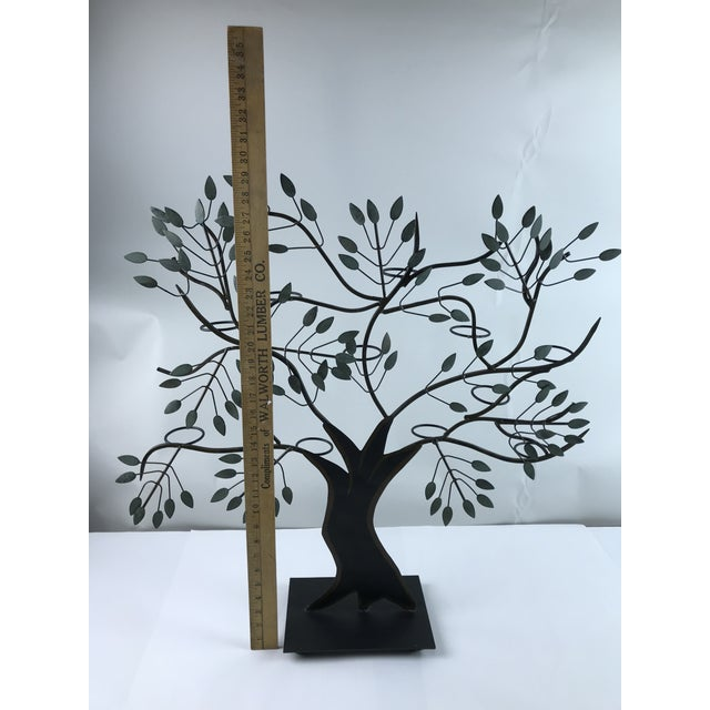 Large hand painted tole tree of life with 11 glass votive holders in the back. Hand painted black with green accents,...