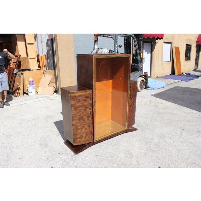 Stunning French Art Deco exotic Macassar ebony vitrine or china cabinet, circa 1940s. Interior completely finished in...