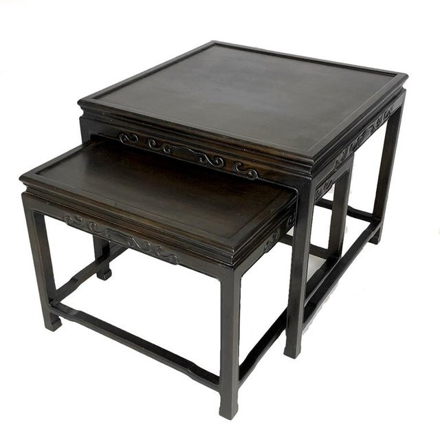 Decorative pair of very usable solid nesting tables with a subtle decorative chinoiserie style. These tables also function...