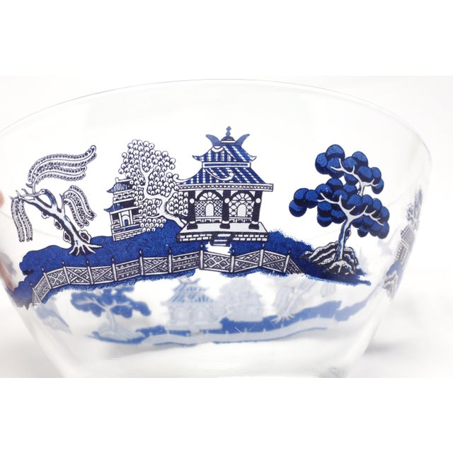 "A vintage, glass serving bowl by Johnson Brothers, with a printed blue and white ""Willow Blue"" pattern, depicting willow..."
