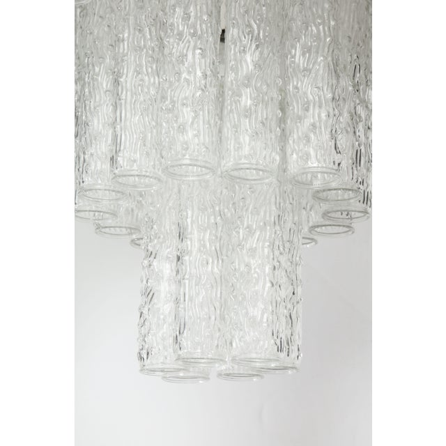 A three-tier chandelier handcrafted in Italy. The piece is made up of a metal frame that supports three tiers of round,...