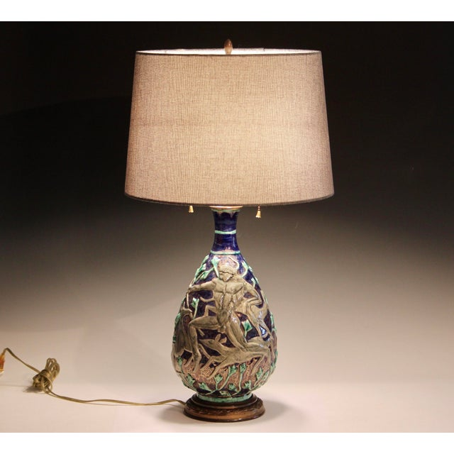 Vintage Jean Mayodon Art Deco pottery lamp decorated with deer and hunters amidst a gilt blue and green forest. Circa...