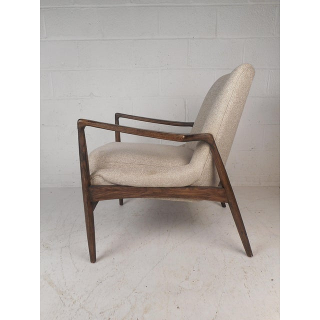 This gorgeous mid-century style lounge chair features a sculpted frame with angled back legs. The high back rest and...