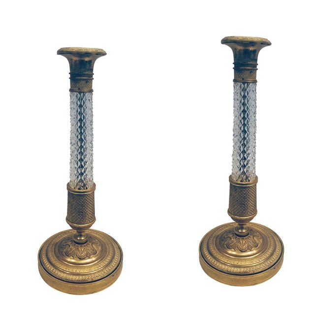 A fabulous pair of Baccarat empire-style bronze doré candlesticks with crystal. Turn of the century, France.