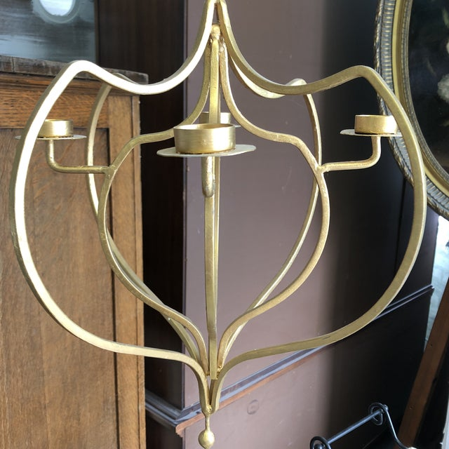 Gold tone contemporary hanging candelabra has a unique and elegant look and a place to burn four candles...stunning in a...