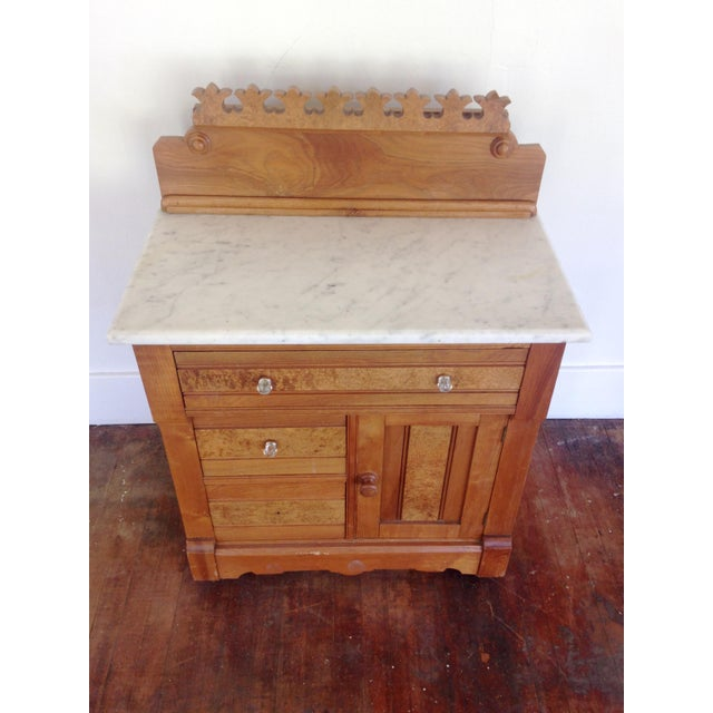 Antique G. Schindler & Co (Portland) wood cabinet with marble top, on caster wheels and burl crown detail. 3 drawers and a...