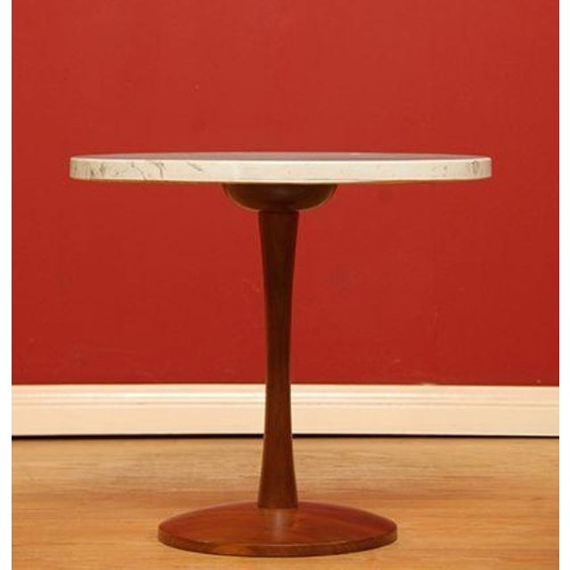 A classic Mid-Century tulip style table made of marble with a wood base. Circa 1960s. An essential addition for any Mid-...