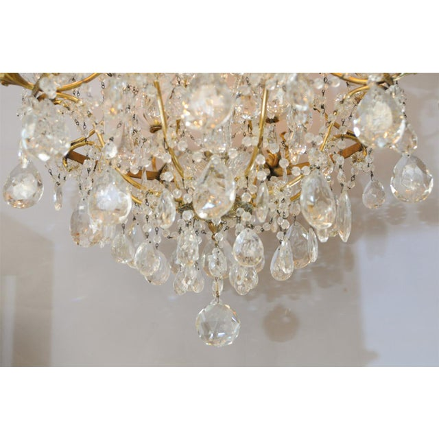 Chandelier, of gilt bronze, consisting of a finely chased ring suspended by shaped arms, finishing with leafy repousse...