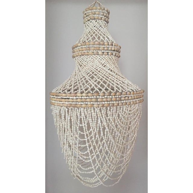 Chandelier style lantern in graceful overlapping layers of tiny beaded shells. This piece has no wiring, it can simply be...
