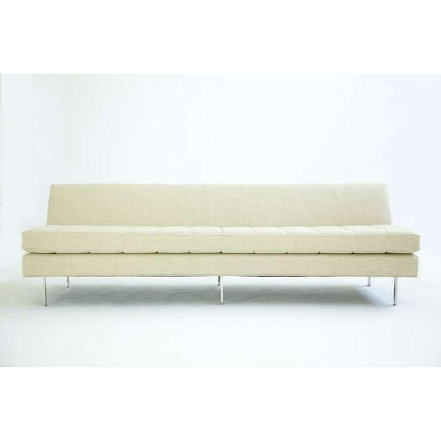 Armless sofa. Tailored clean minimal design. Seat cushion reversible, tufted on both sides. Attached chrome plated legs...