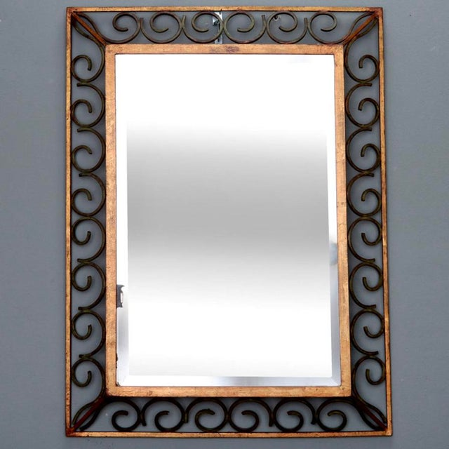 Circa 1930s rectangular beveled edge mirror with open work scroll frame in gilded and green painted iron. Excellent...