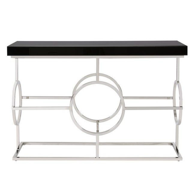 This Console Table features a stainless steel bar frame detailed with a circular design on each side. It is topped by a...